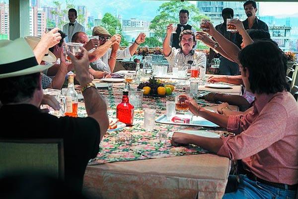 Reunião dos traficantes do cartel de Medellín com o chefe Pablo Escobar (Wagner Moura) na cabeceira |Foto: Divulgação